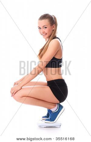 Happy woman on the scales over white background