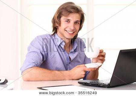 Young businessman taking a break with cup of coffee in his office