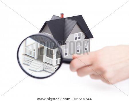 Conceito imóveis - mão segurando a lupa em frente a casa modelo arquitetural, isolat