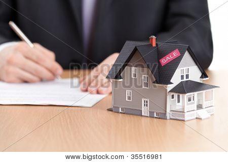 Conceito imóveis - empresário assina contrato por trás do modelo de arquitetura doméstico