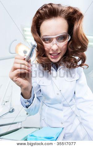 Assistente de dentista está pronto para ajudá-lo a perfurar os dentes cariados