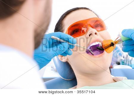 Dentist uses photopolymer lamp to cure carious teeth of the patient