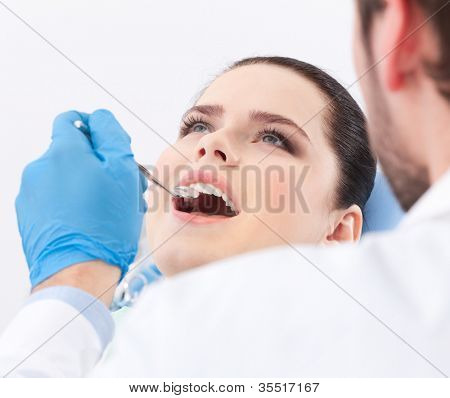 Dentist examines teeth of the patient on the dentist's chair