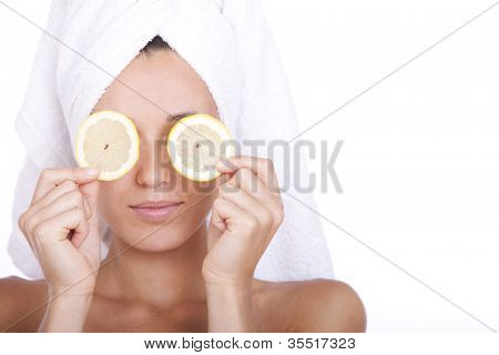 Woman with clean face is holding two slices of lemon over white background
