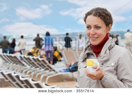 Young girl holding cup on deck of big passenger ship