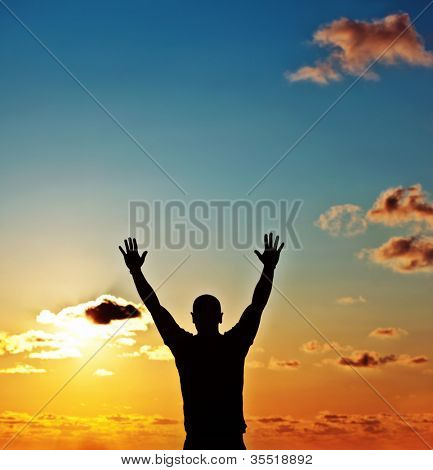 Men silhouette at sunset, human body over natural colorful sky background, hands up having fun, happy healthy guy enjoying nature, travel and freedom, conceptual image of achievement, growth & success