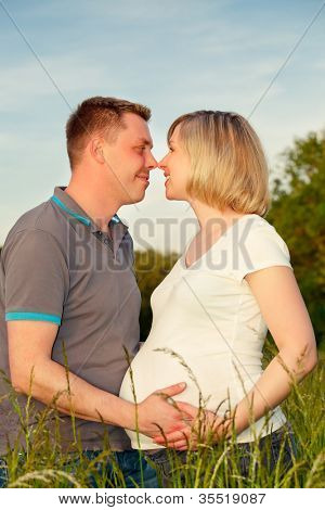 Happy pregnant couple in the park