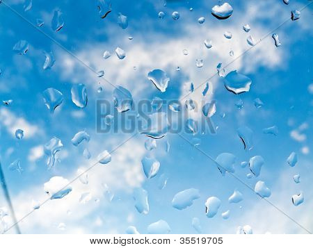 many rain drops during bad weather on a window pane. improvement in the weather. blue sky through the window pane.