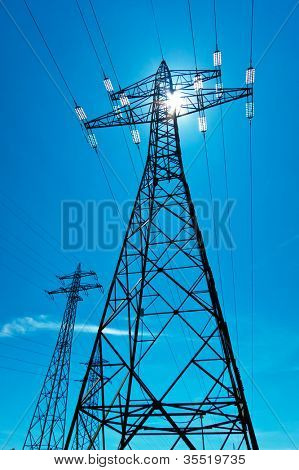 the utility pole of a high voltage line with the sun and blue sky. energy supply from power line.