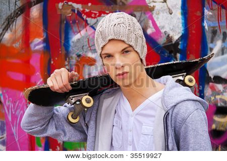 a cool-looking young man in front of graffiti