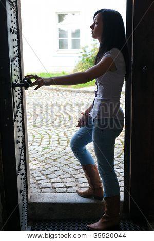 young woman walks through an open door