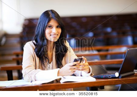 beautiful college student in lecture hall with mobile phone sending sms