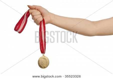 Hand holding gold medal on white