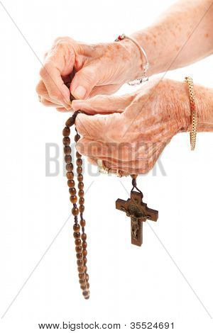 Closeup of senior woman's hands holding Catholic rosary beads.  Isolated on white.  * The traditional religious symbols on the crucifix aren't trademarked or copyrighted.