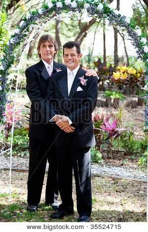 Newly married gay couple posing for a portrait under the wedding arch.