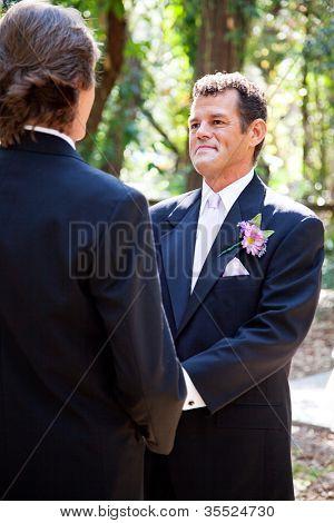 Belo noivo latino-americano se casar com seu parceiro de sexo mesmo em uma cerimônia de casamento ao ar livre.