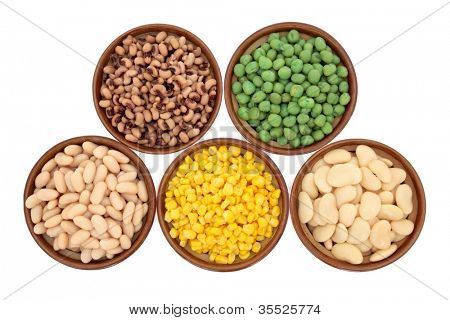 Cooked black eyed and marrowfat mushy peas, butter and haricot beans and sweetcorn selection in rustic earthenware bowls over white background.