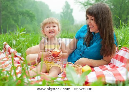mother and daughter have picnic eating apples outdoor