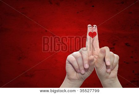 Concept or conceptual human or female hands with two fingers painted with a red heart over a old vintage paper background for valentine,romantic, love,couple,young,family or wedding