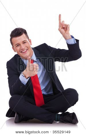 seated young business pointing and showing you something above his head and gibing the ok for it