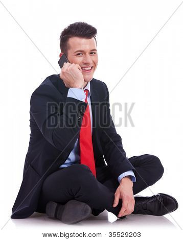 business man  sitting cross-legged on the white background and talking on the phone