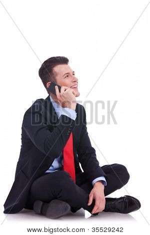 seated young business man talking on the phone and looking at his side on white background