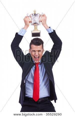 Business man celebrating with trophy over his head on white background