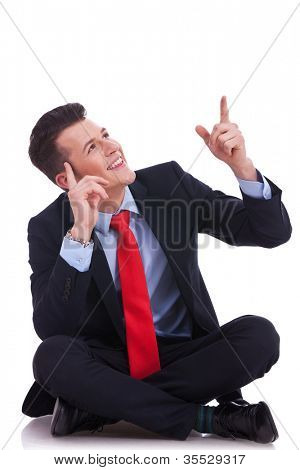 young seated business man looking up above his head and pointing to empy copy space