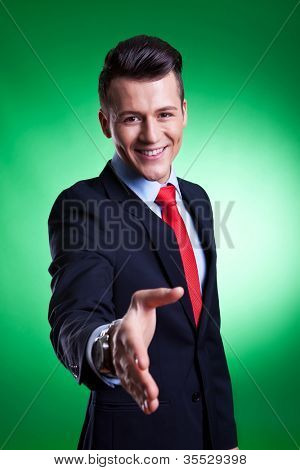 Young business man ready to set a deal by offering a handshake over green background