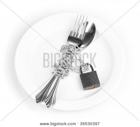 Fork and spoon with chain and padlock on plate isolated on white