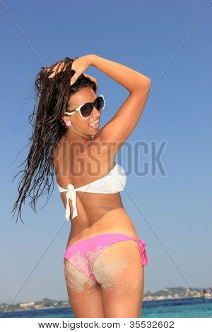 Back view of a young woman enjoying the summer time on the beach