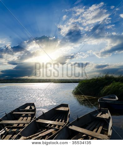 sunset over river with boats