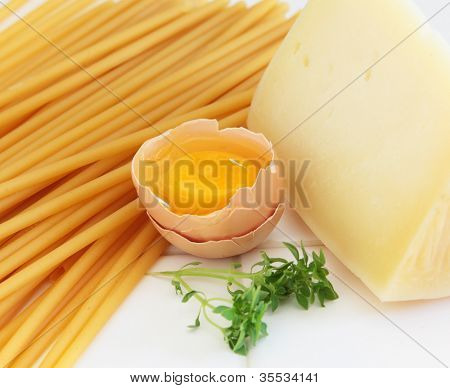 Ingredients for use in a pasta meal, such as pastitsio, macaroni or ziti, raw egg, graviera hard cheese from Crete and Greek small leaved basil.