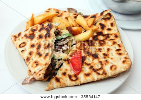 A calzone-style covered pita pie, containing chicken souvlaki meat, salad and cheese, served with french fried potato chips