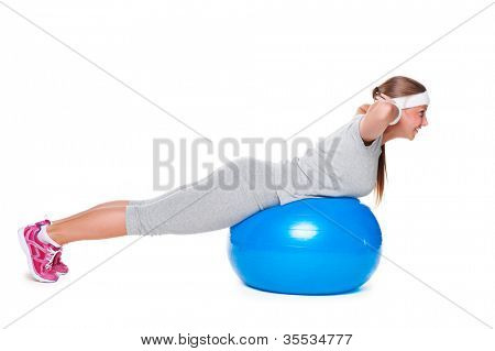 sporty woman doing exercises on blue ball. studio shot over white background