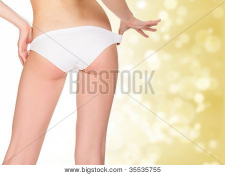 female backside, golden background with blurred lights.