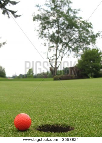 Golf Ball Beside The Hole