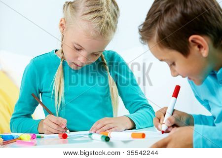 Portrait of lovely girl and boy drawing with colorful pencils