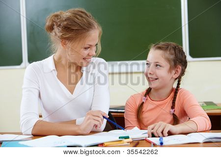 Portrait of lovely girl and her teacher drawing at lesson