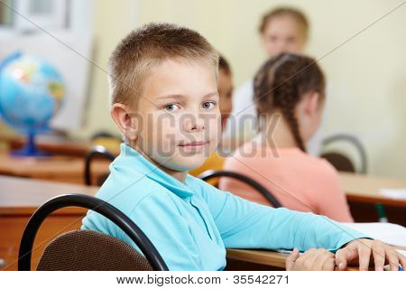 Portrait of smart lad at workplace with classmates and teacher on background