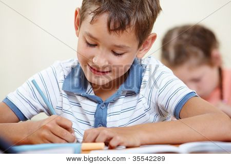 Portrait of smart lad drawing at lesson with classmate on background