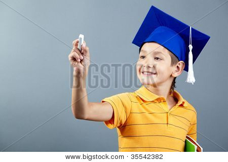 Portrait of cute schoolkid writing with chalk on imaginary blackboard