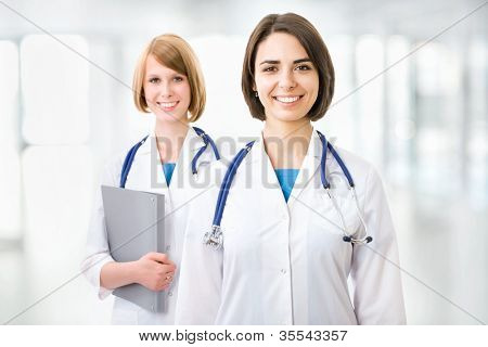 Portrait of two successful female doctors holding a writing pad
