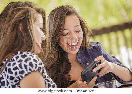 Attractive Mixed Race Girls Smiling and Talking While Working on Smart Mobile Phone and Tablet Computer.