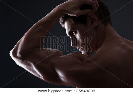 Stylized portrait of handsome muscular man flexing bicep