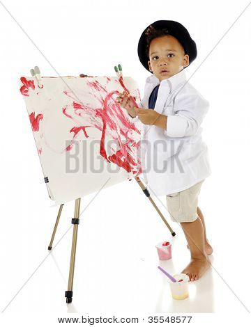 An adorable preschooler looking back at the viewer as he creates his own painted masterpiece.  He has a slightly splattered face and wears a smock and beret.  On a white background.