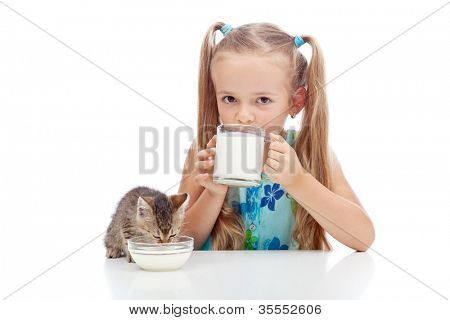 Drinking milk with my best friend - little girl and kitten enjoying dairy product