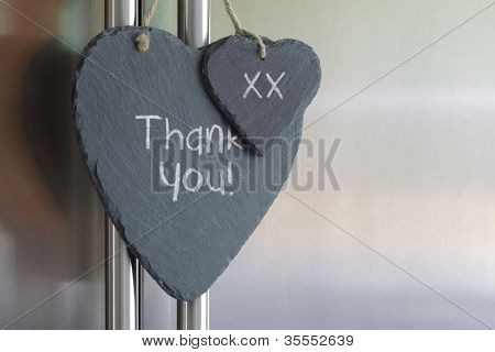 Thank you note written in chalk on a slate heart hanging on a refrigerator door