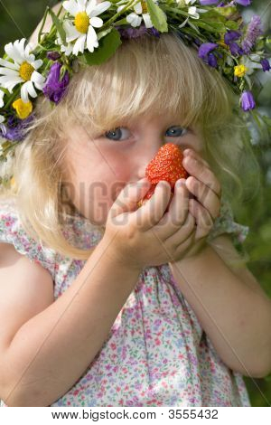 Little Girl In Flowers Wreat With Strawberries In Hands
