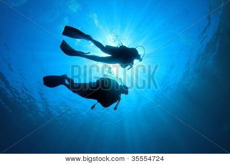 Couple of scuba divers set out on an underwater adventure